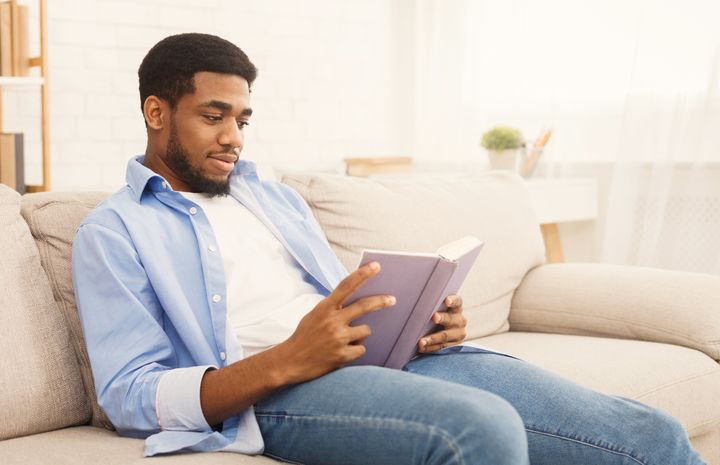 Relaxed african-american man reading book, having rest at home, copy space