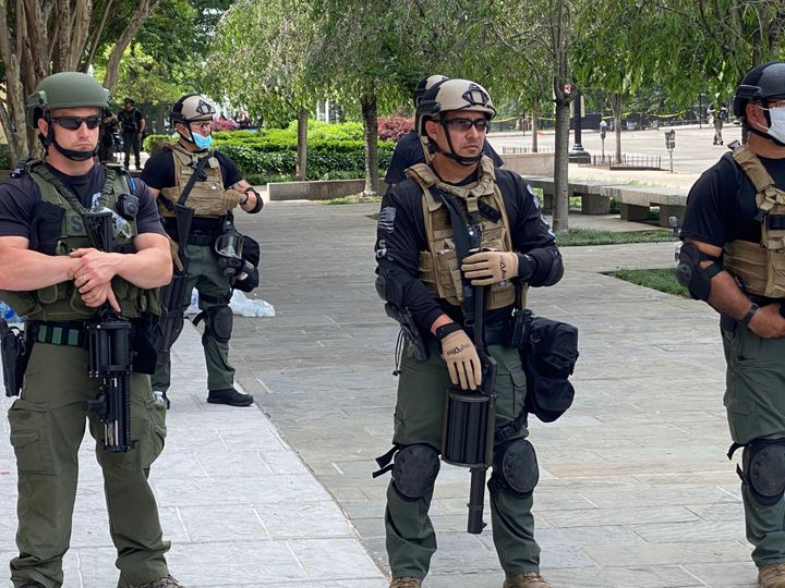 Federal law enforcement officers wear unidentifiable uniforms, some with plain T-shirts under their military-style gear, whil