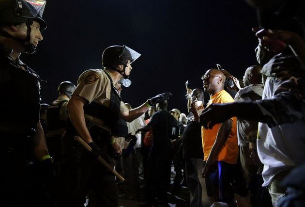 Officers and protesters face off on Aug. 10, 2015, in Ferguson, Mo., after a protest marking the anniversary...