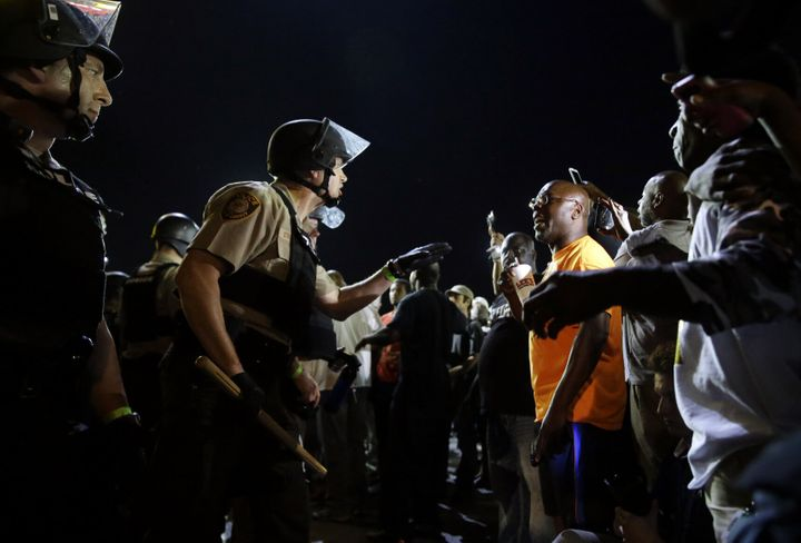 Officers and protesters face off on Aug. 10, 2015, in Ferguson, Mo., after a protest marking the anniversary of Michael Brown's death was punctuated with gunshots.