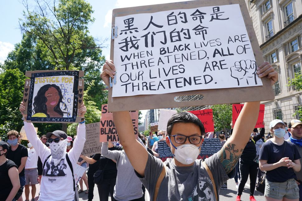 "A protester holding a sign reading ""Black Lives Are All Of Our Lives"" in Chinese and ""When Black Lives Are Threatened, All Of"