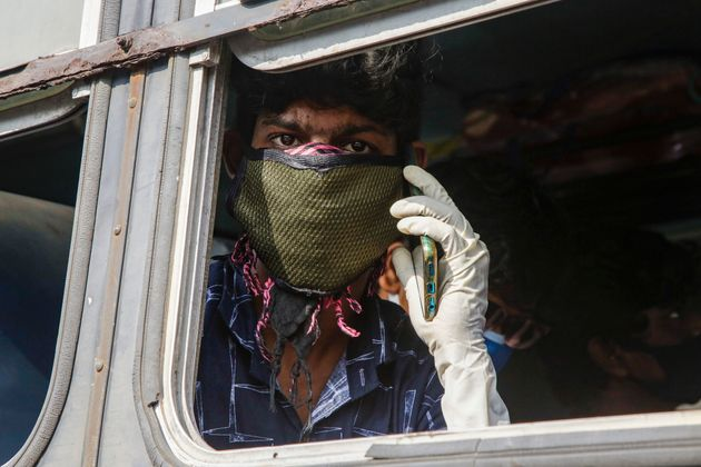 A masked Indian commuter speaks on a mobile phone as he travels in an interstate bus in Kolkata, on Wednesday,...