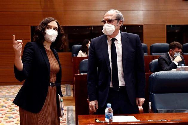 La presidenta de la Comunidad de Madrid, Isabel Díaz Ayuso, conversa con el portavoz socialista, Ángel...