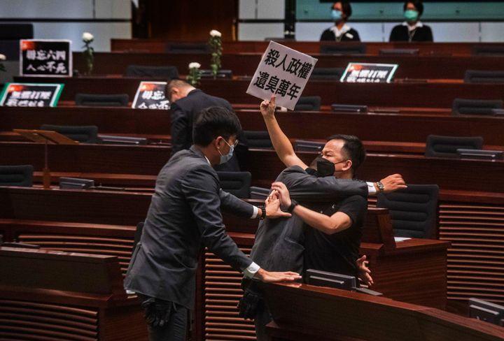 "Pan-democratic legislator Chan Chi-chuen, holding a placard reading ""A murderous regime stinks for ten thousand years,"" scuff"