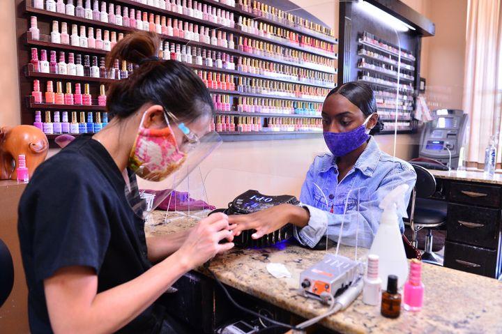 Manicure atende cliente protegida por uma tela de acrílico no Nails and Spa Salon, em Miramar, Flórida, no fim de maio.