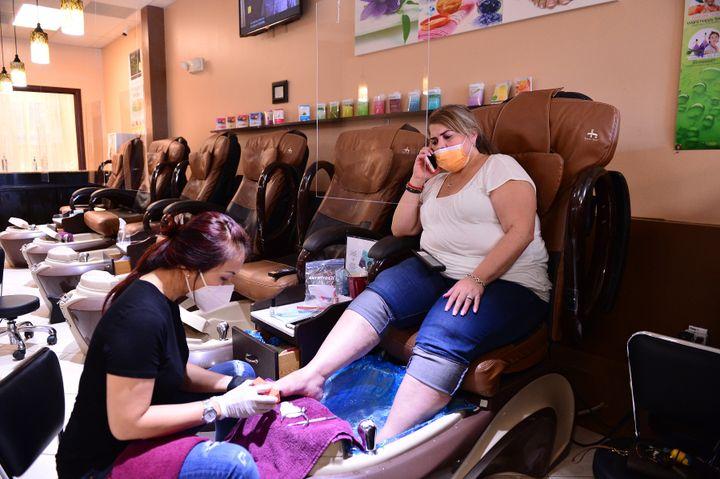 A manicure Jimmie atende uma cliente no salão Nails and Spa, em Miramar, Flórida, 20 de maio de 2020.