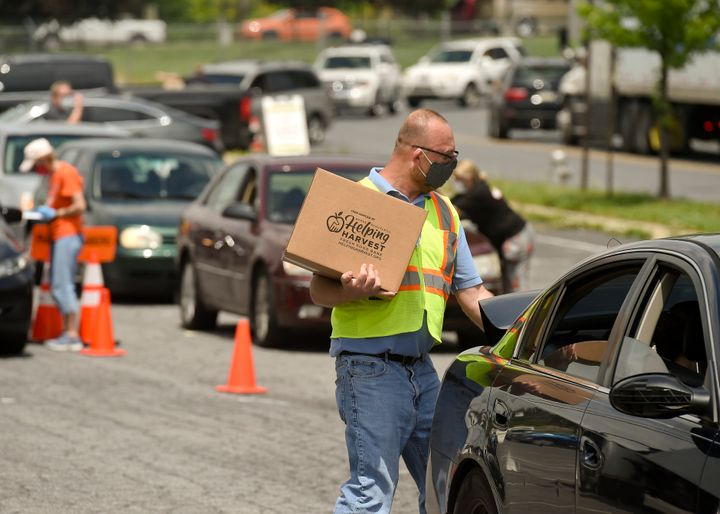 James Walton of Helping Harvest carries a box of food to a car during a pop-up food distribution in Reading, Pennsylvania, on May 29.