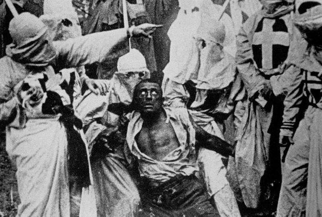 Des membres du Ku Klux Klan s'en prennent à un homme noir dans