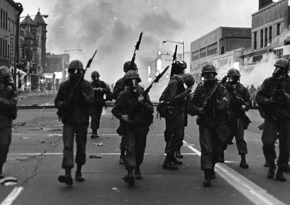 Troops march along a street in Washington in April 1968, responding to protests that turned violent following the assassinati