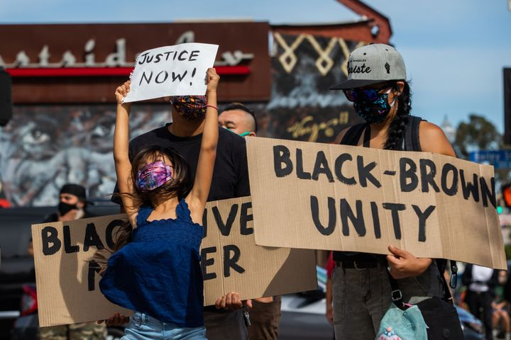 A girl jumps holding a sign while she and her family protest in the Boyle Heights neighborhood of Los Angeles on May 30.
