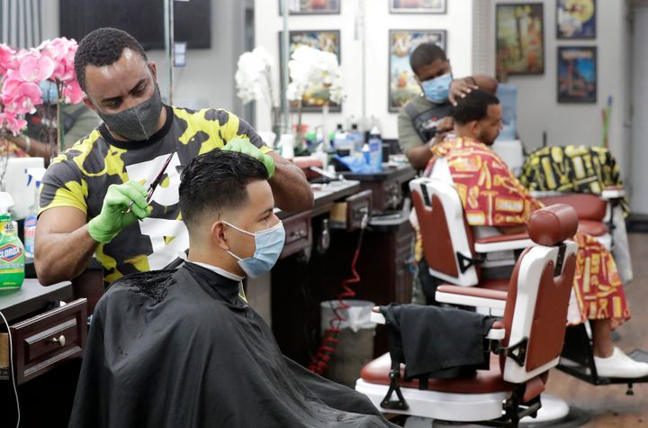 Barbers in  Florida wear masks to protect against the coronavirus while at work on May 21. Personal grooming shops