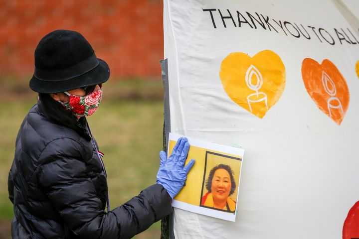 A mourner touches a photo at a memorial of Hiep Bui Nguyen, a Cargill worker who died from COVID-19, in Calgary, Alta. on May 4, 2020.