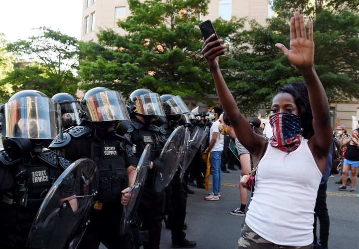 A protester stands, arms in the air, in front of a row of officers during a demonstration near the White House on June 1.