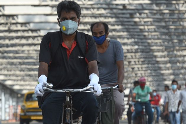 Commuters wear face masks as they cycle over Howrah Bridge at Howrah on June 3, 2020 in