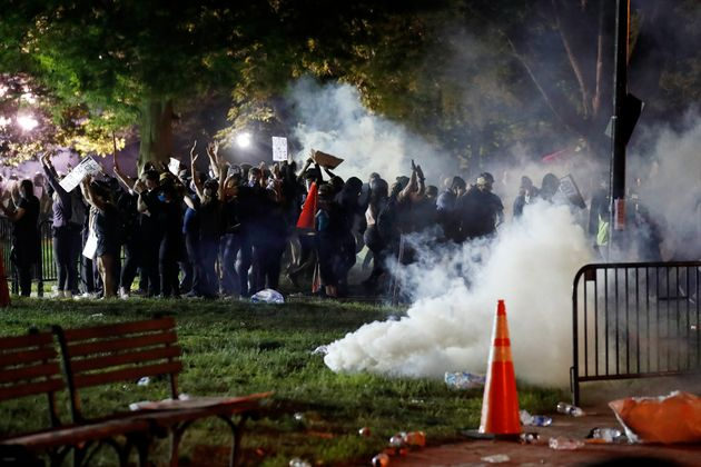 Tear gas billows as demonstrators gather in Lafayette Park to protest the death of George Floyd, Sunday,...