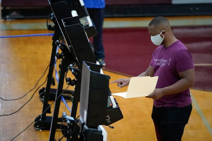 A man votes in Washington, DC's, primary election on June 2, 2020. Many voters had to spend hours waiting in line at polling