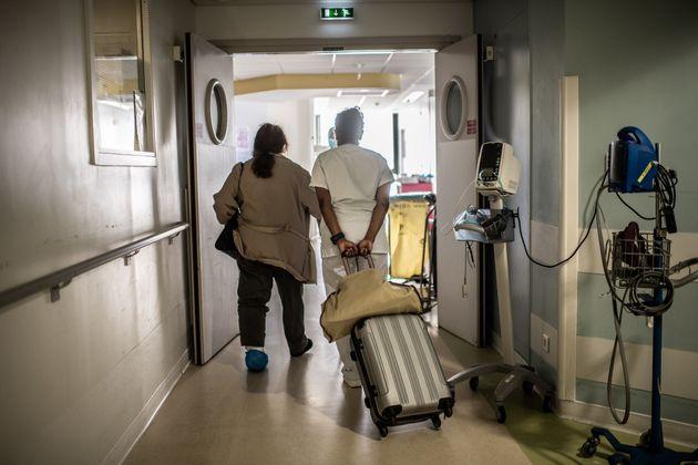 Une infirmière aide une patiente avec sa valise, à l'hôpital Saint-Louis à...