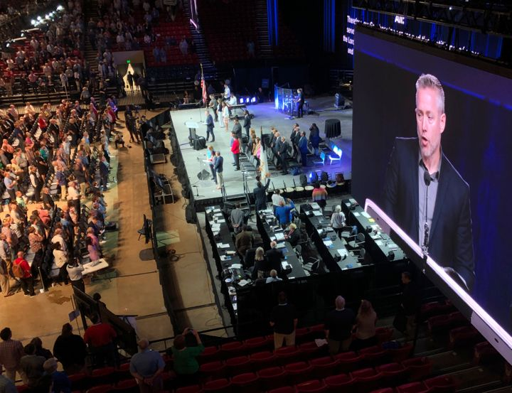 The president of the Southern Baptist Convention, J.D. Greear, is shown on a video screen as he addresses the denominations