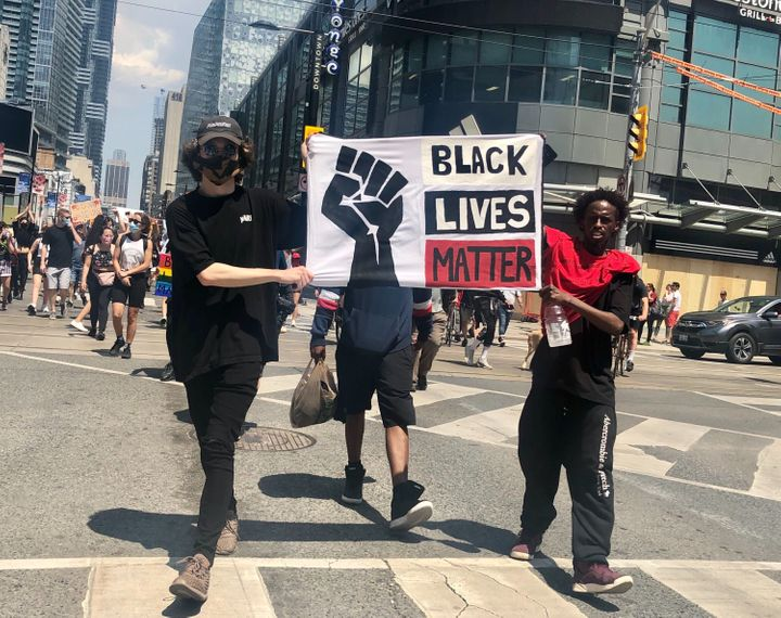Protesters carry a sign at Toronto's March For Change on Friday.