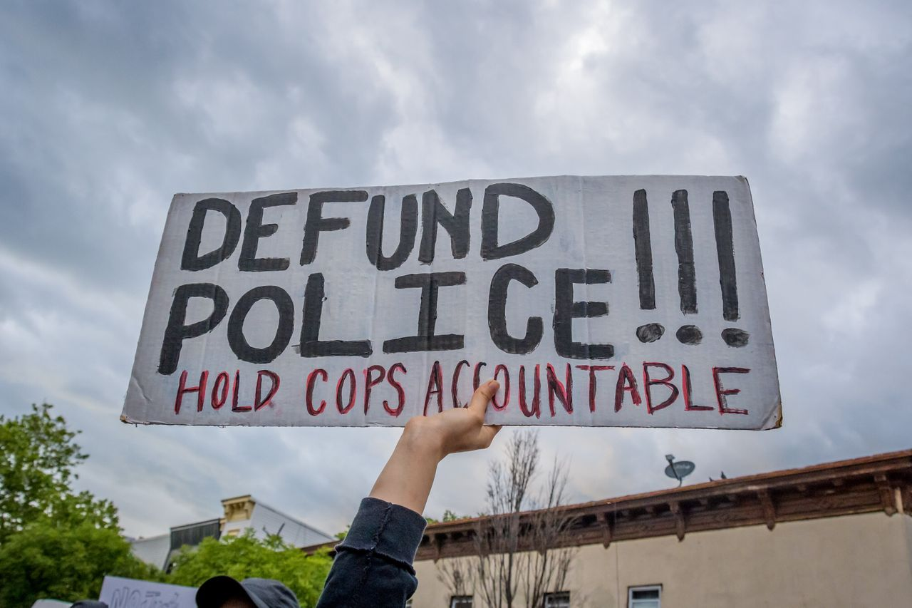 """A participant holding a """"Defund Police"""" sign at a protest. Hundreds of protesters flooded the streets of Crown Heights in Brooklyn, New York, to demand the defunding of the police force and to demonstrate against police brutality in the wake of George Floyd's death."""