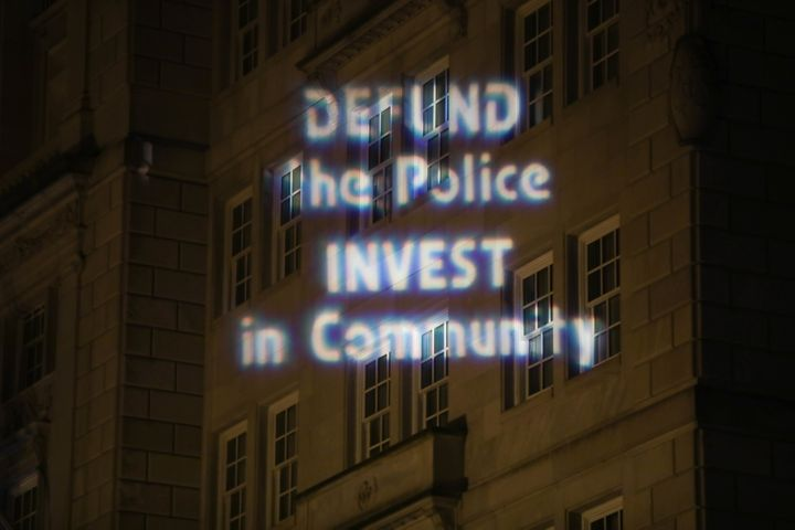 Text is projected Thursday on a building in downtown Washington during a protest over police brutality sparked by the May 25