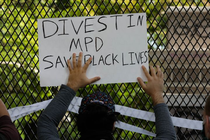A sign to divest in the police department is held up during a Washington, D.C., protest over the death of George Floyd, an un