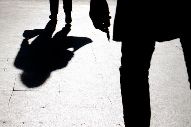 Blurry silhouette and shadow of a woman carrying a bag and a man holding sharp object following her,...