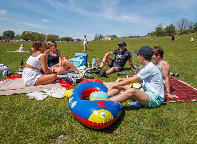 People enjoy the hot weather on the banks of the River Wharfe in Burnsall, Yorkshire, as people flock...