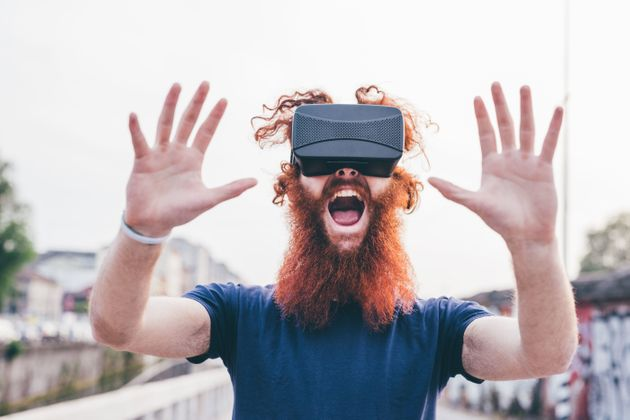 Portrait of young male hipster with red hair and beard screaming whilst wearing virtual reality