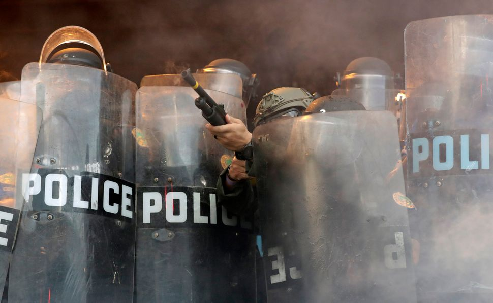 A police officer fires rubber bullets at protesters during a demonstration next to the city of Miami Police Department on May