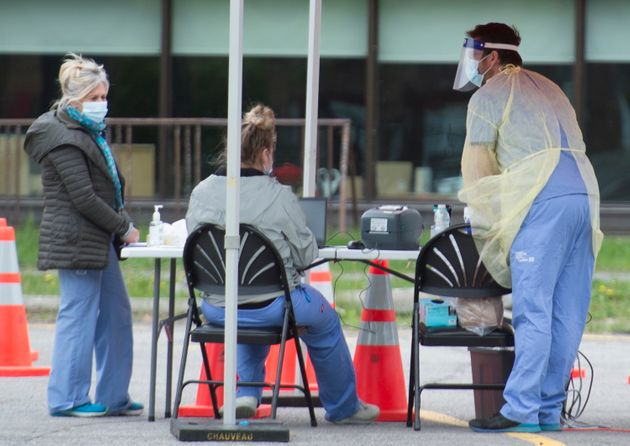 Des travailleurs de la santé attendent que des gens soient testés dans une clinique mobile de dépistage...
