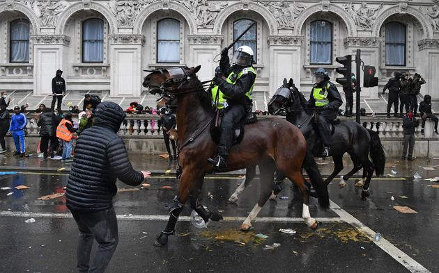 A mounted police officer raises their baton as police horses ride along Whitehall in an attempt to disperse