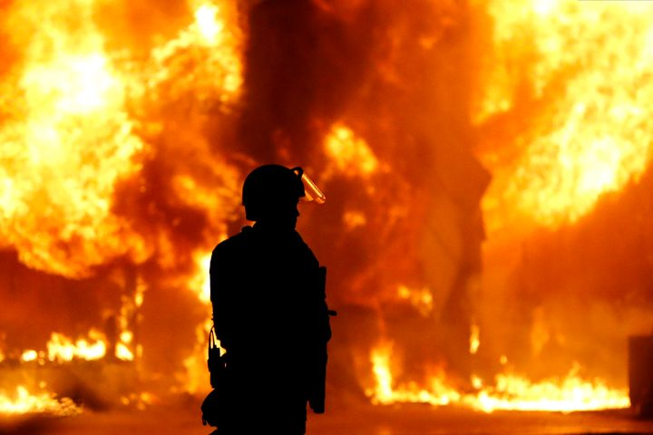 A Minneapolis Police officer stands near a structure fire, Saturday, May 30, 2020, in Minneapolis. Protests continued followi