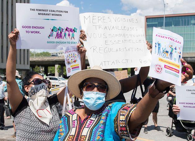 Des gens brandissent des pancartes lors d'une manifestation devant le bureau de circonscription du premier...