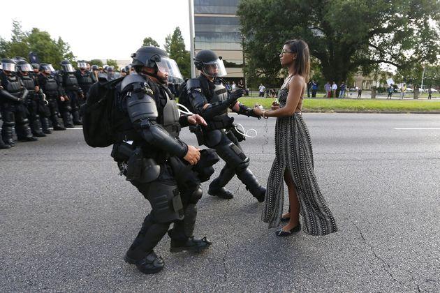 武装した警察官に対して、無言で抗議する黒人女性。2016年、ルイジアナ州バトンルージュでの黒人射殺事件に対するデモの際に撮影され「象徴的だ」と話題になった。