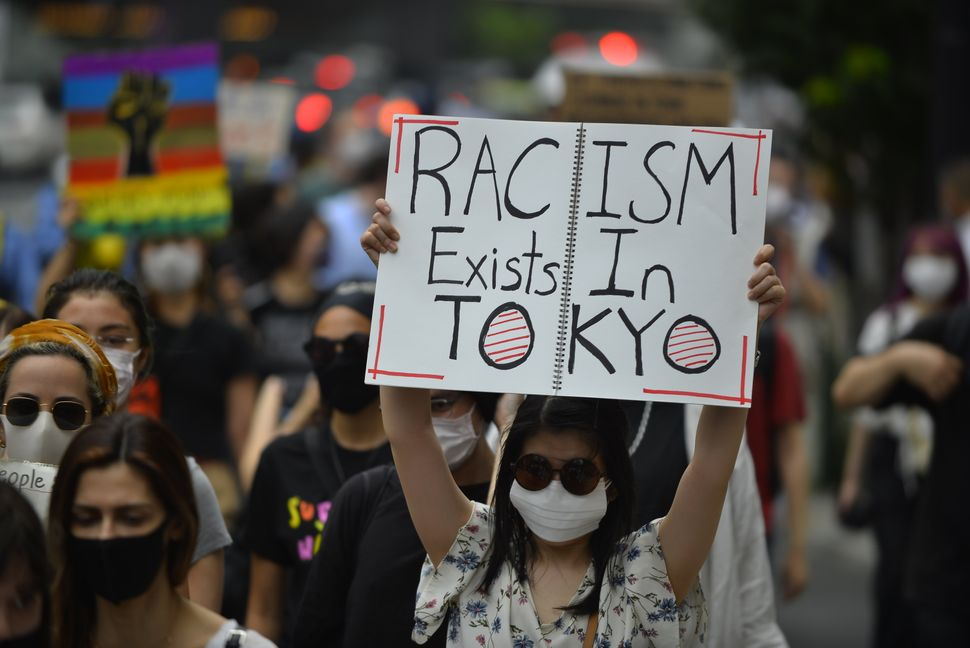 "A demonstrator holds up a sign that reads ""Racism exists in Tokyo"" at a Saturday protest in Tokyo."