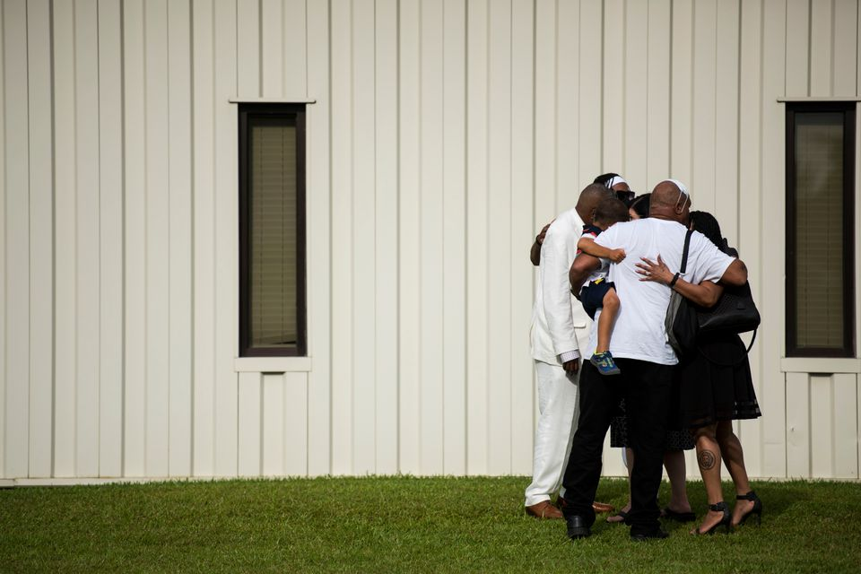 A group of people exiting a memorial for Floyd embrace each other outside the R.L. Douglas Cape Fear...