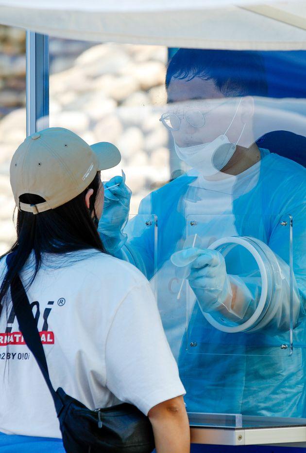 30일 서울 영등포구 자매근린공원에 마련된 신종 코로나바이러스 감염증(코로나19) 워킹스루 현장선별진료소에서 의료진이 검체채취를 하고