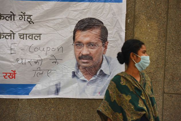 A woman wearing facemask seen next to a poster of Delhi Chief Minister Arvind Kejriwal during a community...