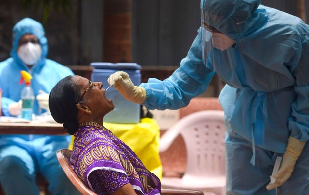 A doctor takes a swab sample of a resident at a coronavirus testing drive inside Dharavi during a government-imposed...