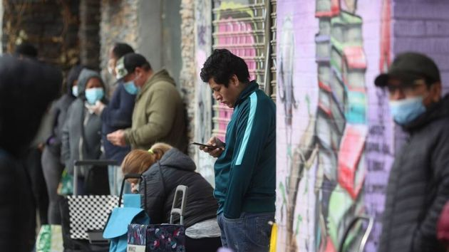 Vecinos de Aluche, Madrid, hacen cola para recoger alimentos
