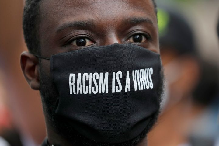 A protester wears a face mask in front of the U.S. embassy, during the Black Lives Matter protest rally in London, Sunday, Ju