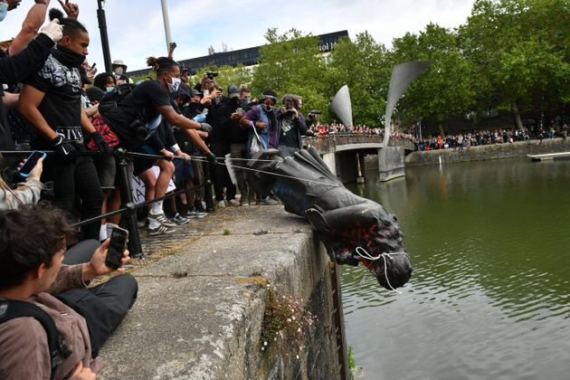 Protesters throw statue of Edward Colston into Bristol harbour during a Black Lives Matter protest in...
