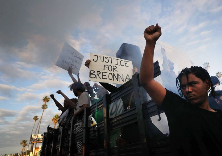 "Protesters demonstrate against racism in Los Angeles on Sunday. One protester is holding a sign ""Justice for Breonna."""