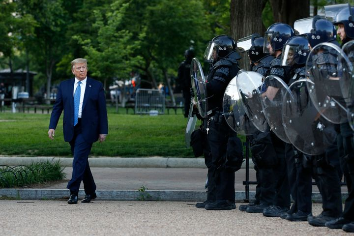 President Donald Trump walks past police in Lafayette Park after visiting St. John's Church across from the White House on Mo