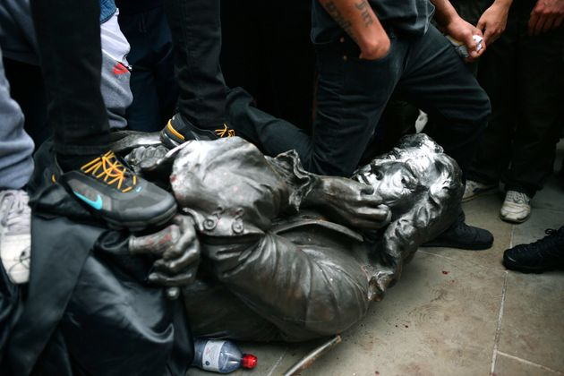 The statue being knelt on by protesters during Sunday's