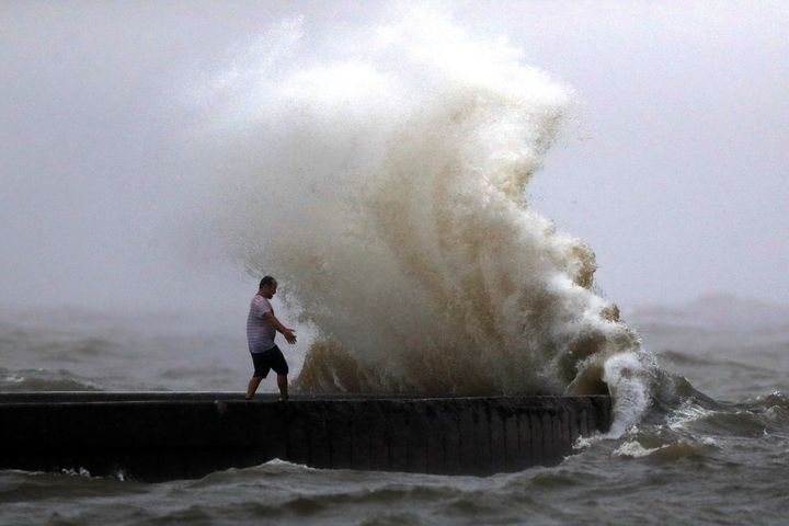 A wave crashes as a man stands on a jetty near Orleans Harbor in Lake Pontchartrain in New Orleans on June 7, 2020, as Tropic