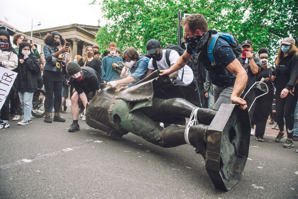 Protesters rolling the statue of slaver Edward Colston towards Bristol's