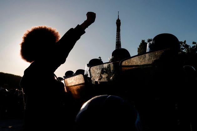 Des manifestants lèvent le poing devant les policiers anti-émeutes lors d'une manifestation...