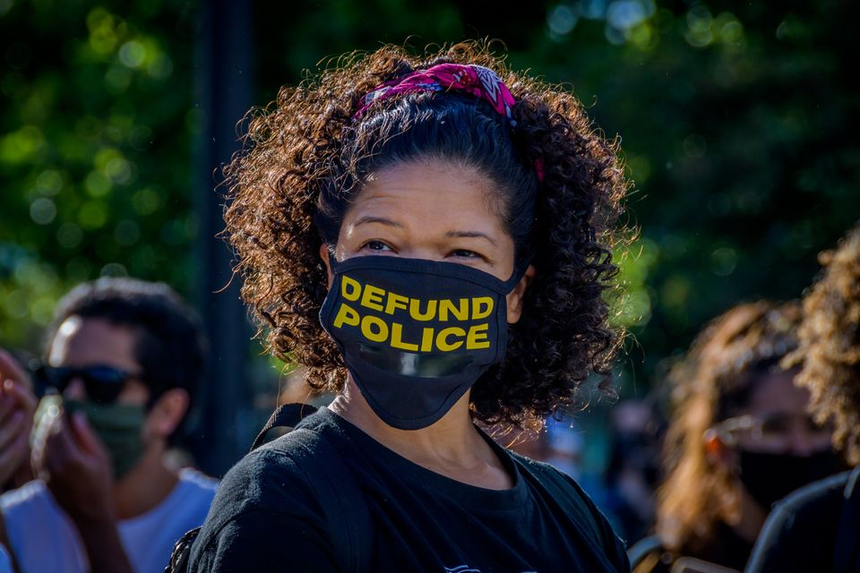 À New York, dimanche 7 juin, une manifestante arbore un masque contre le coronavirus orné...
